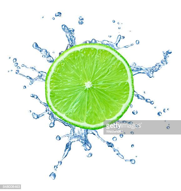 Slice of lime with water splash in front of white background