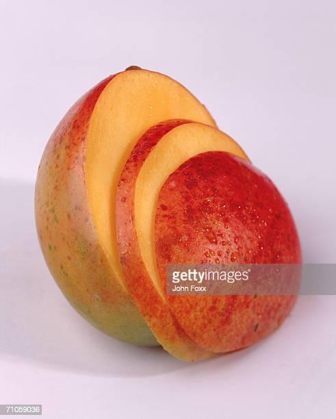 Slice of mango on white background, close-up