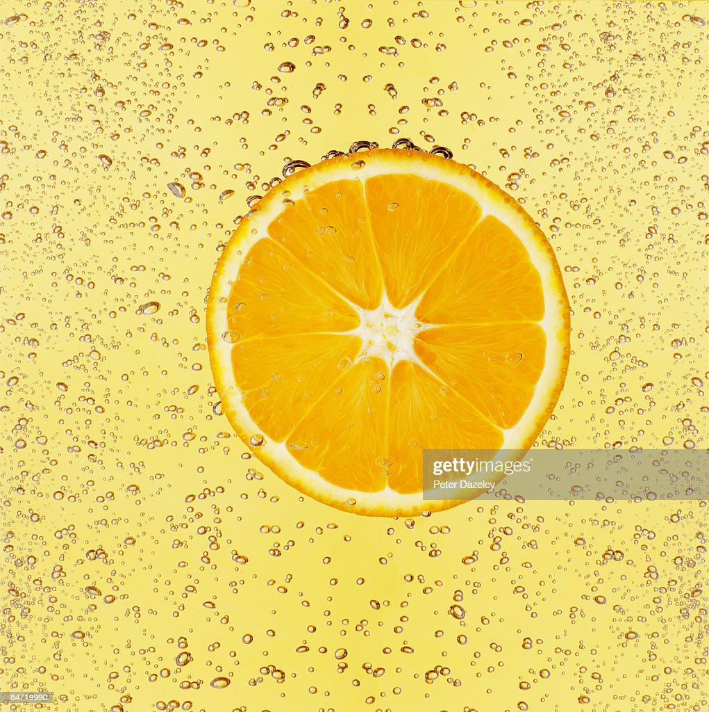 Slice of orange in water with bubbles
