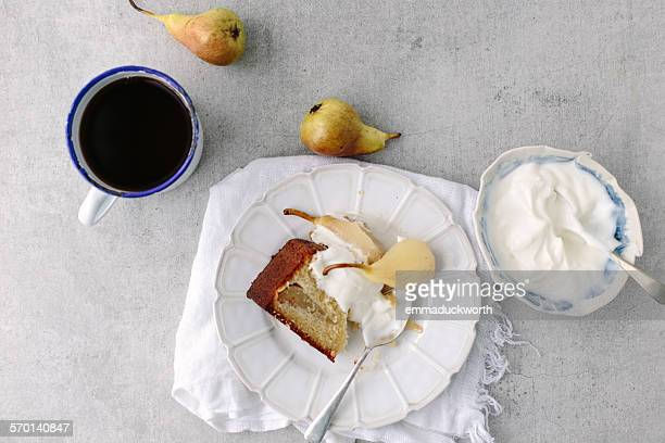 Slice of pear sponge cake with cup of black tea