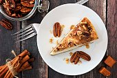 Slice of pecan caramel cheesecake, top view on a rustic wooden background