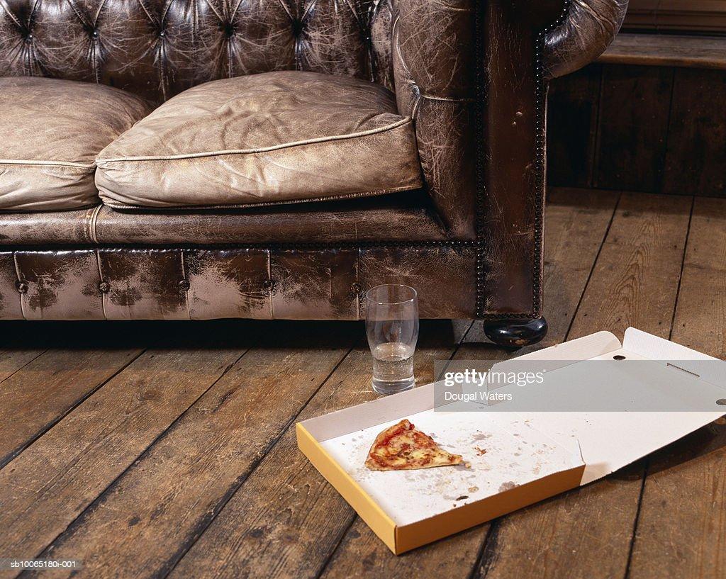 Slice of pizza in box on floor in living room