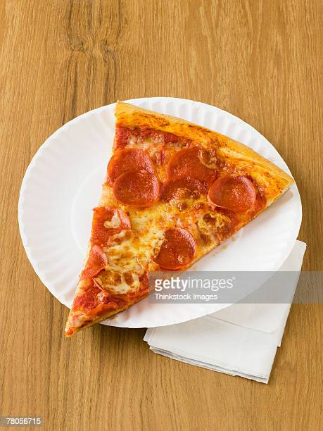 Slice of pizza on a paper plate