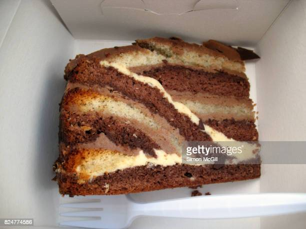 A slice of Puzzle Cake in a white cardboard box
