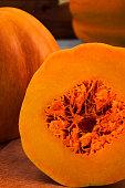 Slice of ripe pumpkin with fibers in the core and flesh orange.