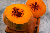 Slice of ripe pumpkin with orange flesh and fibers in the core.