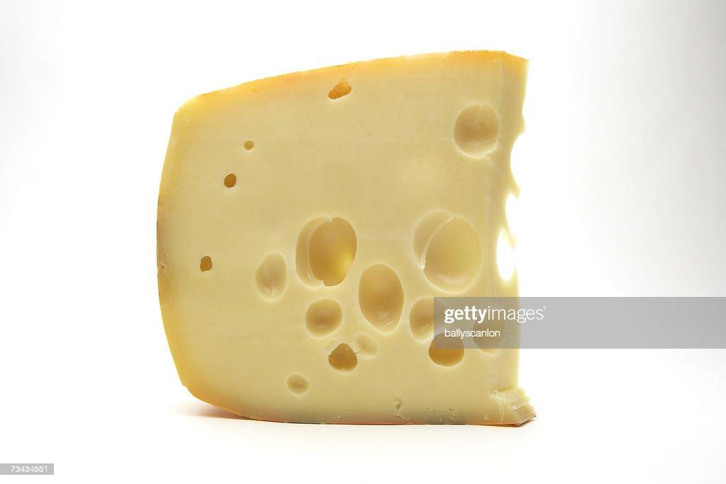Slice of swiss cheese on white background : Stock Photo