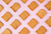 Toasted bread on soft pink background.