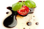 slice tomato and basil  over olive oil and balsamic vinegar on white background