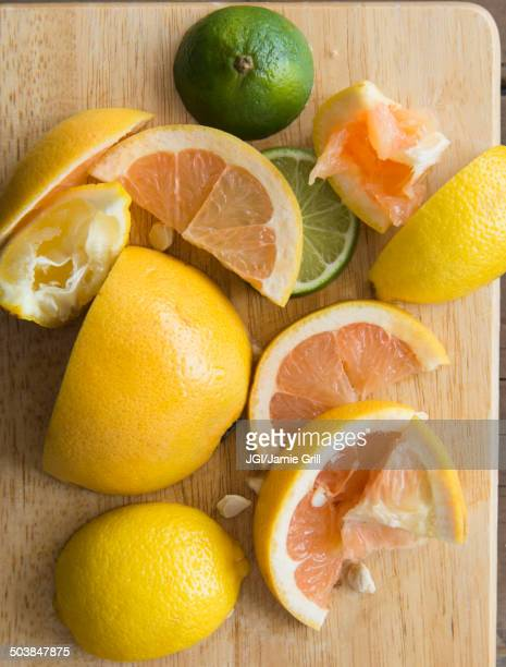 Sliced and squeezed fruit on wooden board