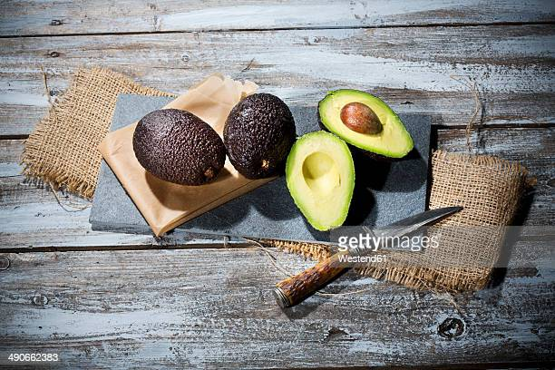 Sliced and whole avocados (Persea americana), baking paper, knife and slate on jute and wooden table
