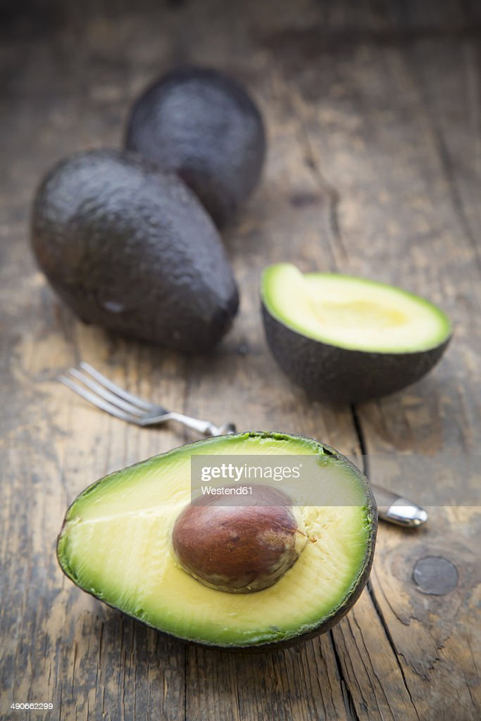 Sliced and whole avocados (Persea Americana) on wooden table