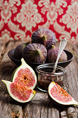 Sliced and whole figs and glass of fig jam on wooden table