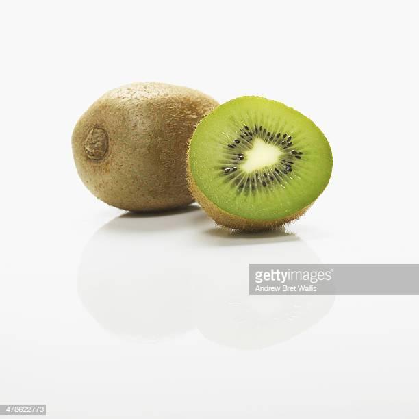 Sliced and whole kiwi fruit against white