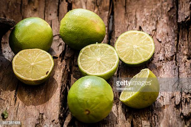 Sliced and whole limes on bark