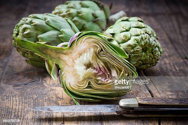 Sliced and whole organic artichokes and kitchen knife on wooden table