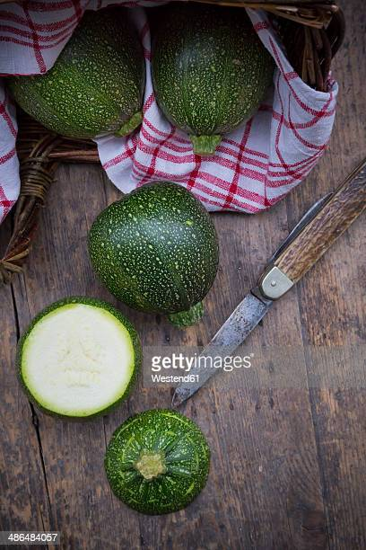 Sliced and whole round courgettes, kitchen towel and a pocket knife on dark wooden table