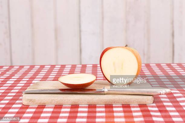 Sliced apple and a knife on wooden kitchen board and red-white checked cloth