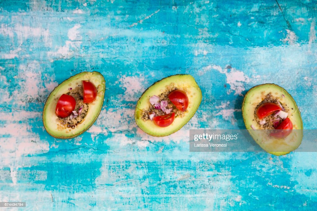 sliced avocado filled with quinoa, cherry tomatoes and red onion : Stock-Foto