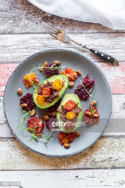 sliced avocado filled with red quinoa and tomatoes