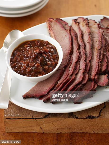Sliced barbecued brisket served with beans, close-up