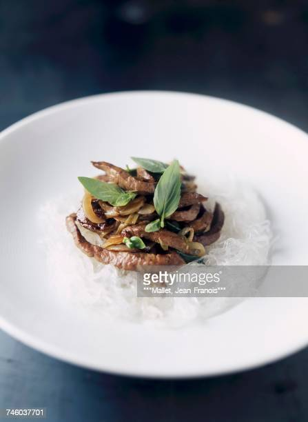 Sliced beef with Thai basil on a bed of rice vermicelli