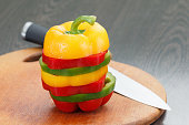 Fresh sliced vegetable bell peppers on wooden cutting board