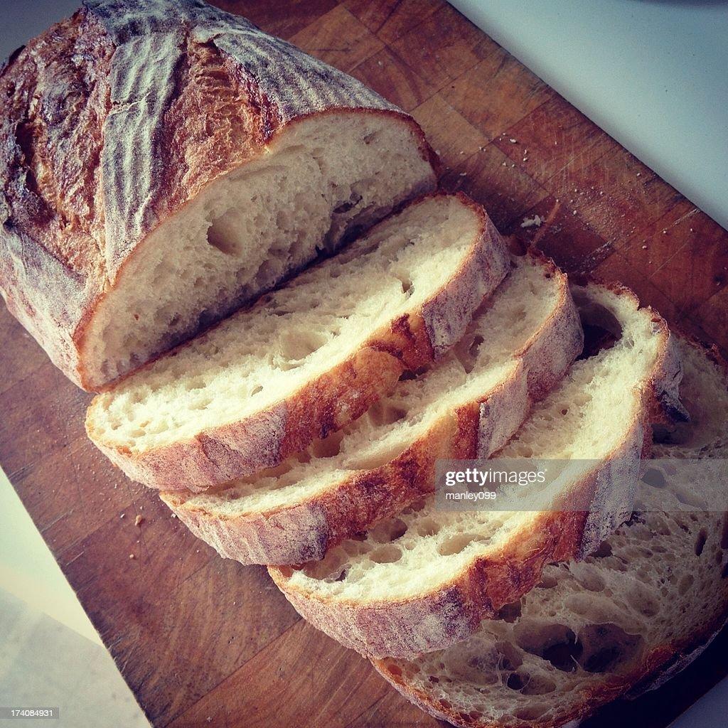 sliced bread loaf on wooden cutting board