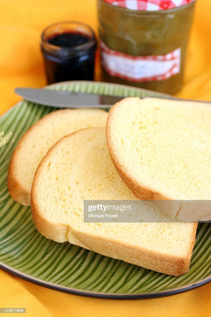 Sliced bread with home made jam on green plate : Stock Photo