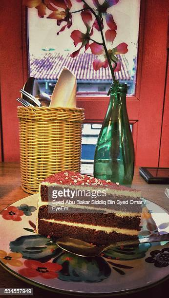Sliced Cake With Flower Vase On Table At Home