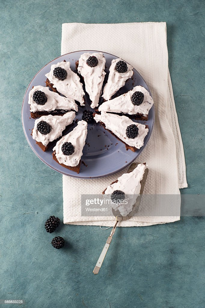 Sliced chocolate cake with creme and blackberries