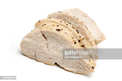 Sliced cooked chicken breast against white