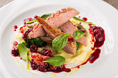 Sliced Grilled Duck breast with potatoes puree and broccoli with cherry sauce on white plate
