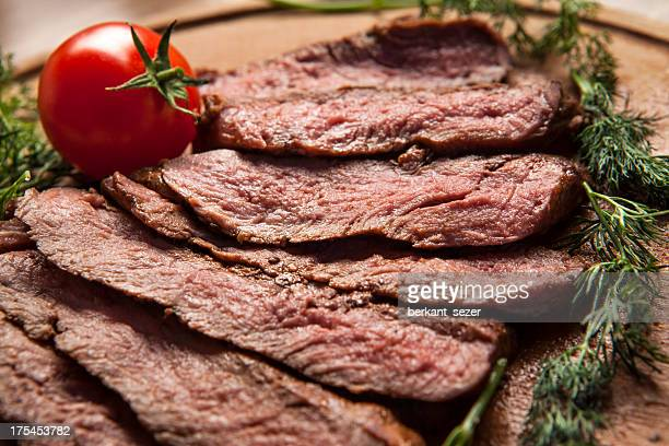 Sliced grilled meat displayed on wooden cutting board