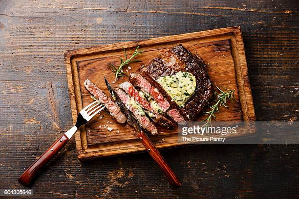 Sliced grilled Medium rare steak Ribeye with herb butter on cutting board on wooden background