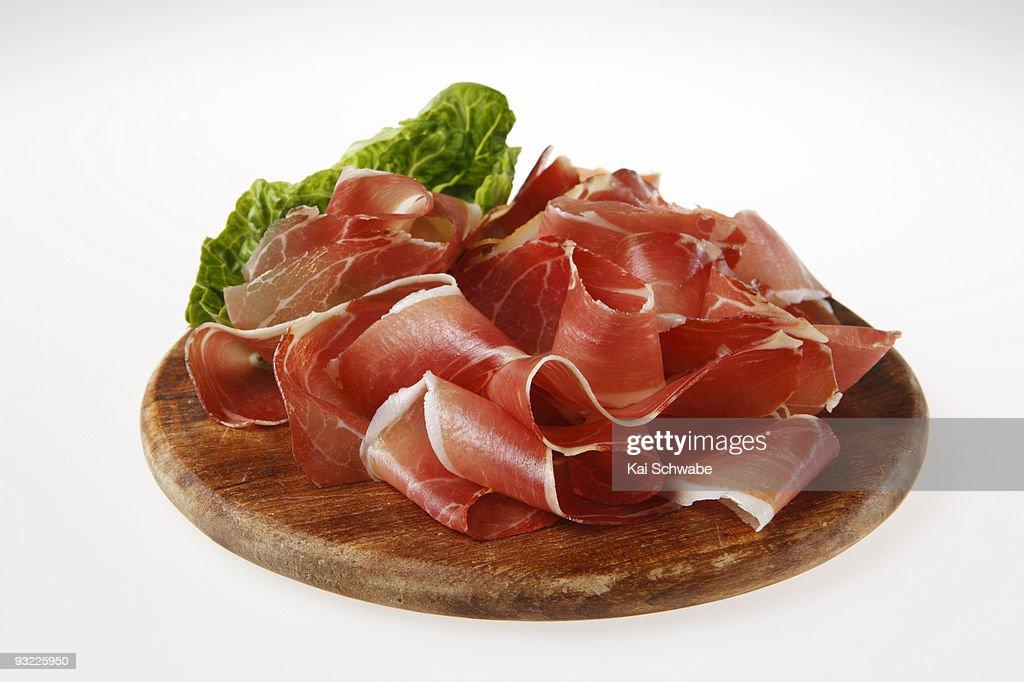 Sliced ham on wooden board, close-up