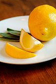 Sliced lemon with mint on white plate.