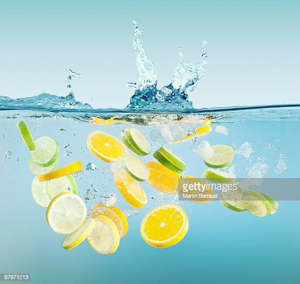 Sliced lemons and limes splashing in water