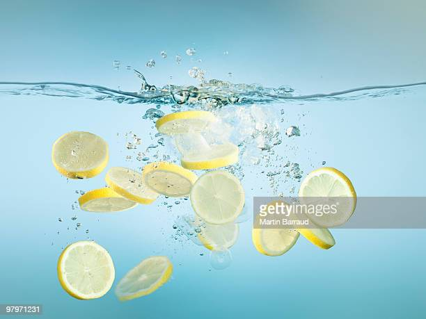 Sliced lemons splashing in water