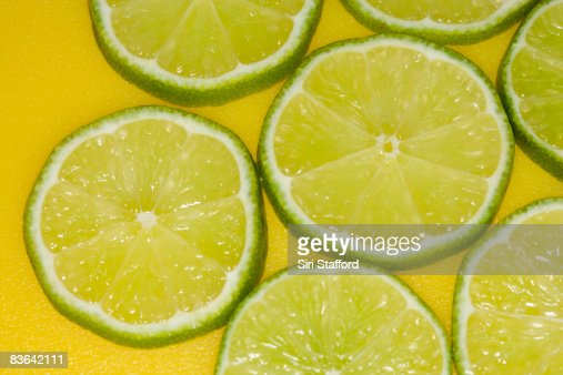 sliced lime on yellow : Stock Photo
