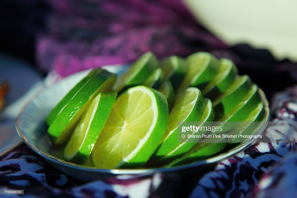 Sliced limes on plate : Stock Photo