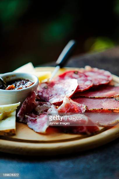 Sliced meat and cheese on chopping board