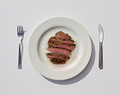 Sliced undercooked meat in plate, fork and knife on the white background.
