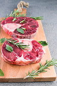 Sliced meat on a wooden board with herbs and spices. Raw meat on the bone close-up. Gray background