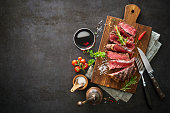 Sliced medium rare grilled beef ribeye steak on cutting board on dark background