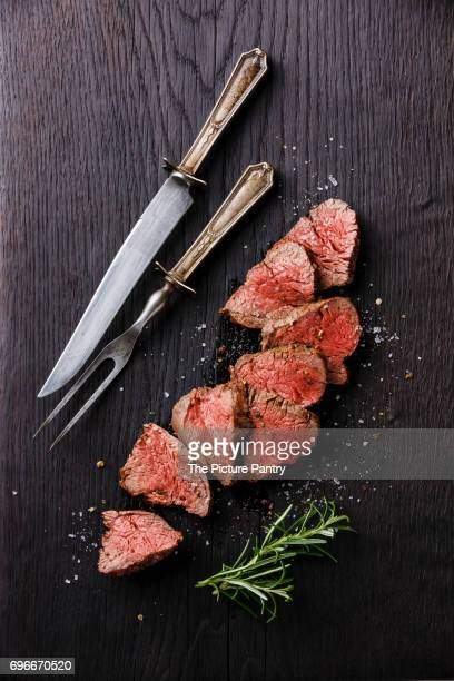 Sliced medium rare Roast beef with table knife and fork for meat on dark background