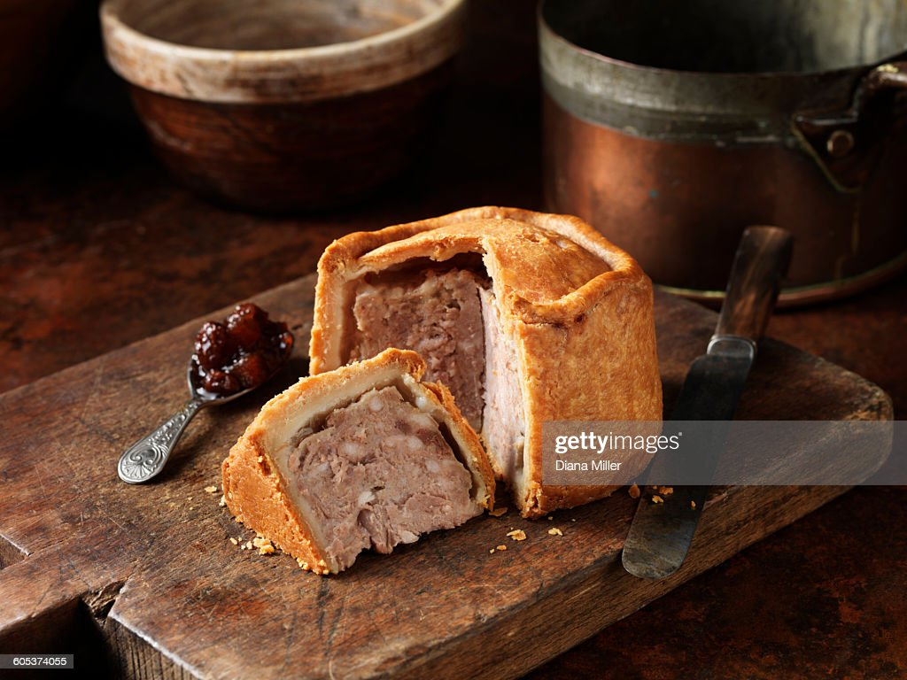 Sliced Melton Mowbray pork pie with spoonful of pickle on wooden cutting board : Stock Photo