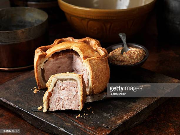 Sliced Melton Mowbray pork pie with wholegrain mustard on wooden cutting board