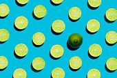 This is a fun brightly lit and colorful overhead photograph of sliced open geen limes lined in rows with a harsh shadow on a blue background.. There is one whole lime symbolizing individuality and bei