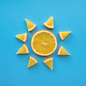 Creative concept made from sliced orange like sun. Blue background. Flat lay. Sun shape.
